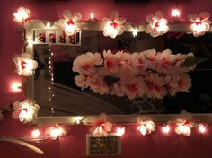 DIY Flower String Lights: Buy a desired length of standard Christmas lights. Then buy a fabric flowered Lei (I bought mine from Daiso for $1.50) of your ideal color. Cut the Lei and pull out the flowers. Make a small cut in the center of the flower large enough so that you can push the flower over the bulb. I double layered mine for an extra-full looking flower. Enjoy!