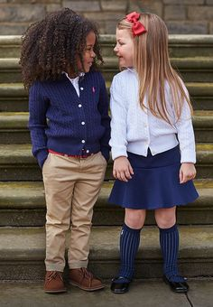 Girls wear cable-knit cardigans with chino & skirt Toddler School Uniforms, Back To School Uniform, School Uniform Outfits, Cute School Uniforms, Kids Uniforms, School Girl Outfit, Uniform Ideas, Police Uniforms, Cute Little Girls Outfits