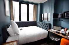 8 Small Hotel Rooms That Maximize Their Tiny Space | This tiny hotel room has a bed that doubles as a couch during the day, a desk, and a fully stocked mini fridge. Unique decor like the speakers, the bright mini fridge, the wrap around headboard, and the industrial-style shelving give the space personality and life to make it a more customized space.