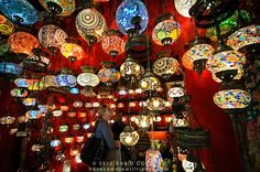A shopkeeper shows a customer his wares. Istanbul's Grand Bazaar includes many stores selling brightly colored hanging lights with a teardrop design of colorful glass mosaics. Grand Bazaar Istanbul, Turkey Photos, Turkish Lamps, Hanging Lights, Mosaic Glass, Colored Glass, Lanterns, Beautiful Places, Holiday Decor