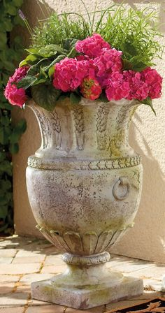 "Standing a grand 30"" tall, this Avignon Vessel Outdoor Planter is an imposing garden urn. Adorned with garland, leaf, and petal trims and ring-shaped faux handles, this decorative outdoor planter makes a bold statement with or without a potted plant."