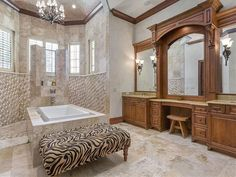 Huge ceilings and marble tile in this high-end bathroom contrast the wide bathroom vanity. The wood construction of this designer bathroom vanity pairs well with the natural stone tile.