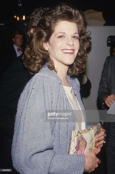 A candid portrait of actor and comedian Gilda Radner smiling. She is holding a purse printed with an Asian design.