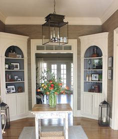 design indulgence: BEFORE AND AFTER OF THE FOYER- grass cloth on walls; paintiing back of bookcases