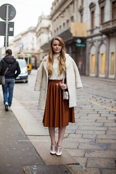 25 Ways to Wear Midi Skirts - rust orange pleated mini skirt worn with an over-the-shoulder fuzzy off-white winter coat + white heels | StyleCaster
