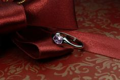 Exotic pink sapphire set in modern white gold engagement ring.