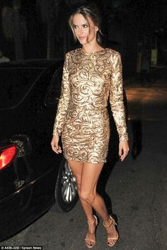 Dipped in gold: Alessandra Ambrosio bared her legs in a gold-sequin mini dress at Sao Paulo Fashion Week in Brazil Tuesday night