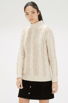 This hand-knitted jumper is constructed from a chunky knit with stretch and features a turtle neck, rubbed cuffs an a cable knit design. Length of jumper from shoulder seam to hem; 66cm approx. Height of model shown 5ft 10inches/178cm. Model wears: size S.