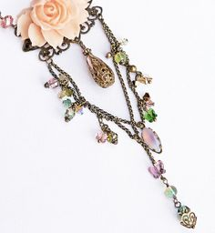 Romantic flower necklace, one of a kind, created with Victorian, Shabby Chic, and Gypsy/Boho femininity in mind. The hand patinaed brass chains are amply adorned with scintillating, wirewrapped Swarovski crystals, pearls, butterflies, vintage Czech glass beads, and antique bronze brass filigree. The delicate pale peach resin peony is warmly complimented by the lush variety of colors, such as emerald and sage greens, lavender, blush rose, pink, and yellow.