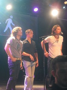 Hanson is an American pop-rock band from Tulsa, Oklahoma formed by brothers Isaac (guitar, piano, vocals), Taylor (keyboards, piano, guitar, drums, vocals), and Zac Hanson (drums, piano, guitar, vocals). They are best known for the 1997 hit song MMMBop from their major label debut album Middle of Nowhere, which earned three Grammy nominations. Despite the enormous commercial success of Middle of Nowhere, the band suffered from the merger that eliminated their label, Mercury Records.