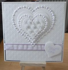 hand crafted Valentine/love card ... white on white ... lots of texture: embossing folder, layered die cuts, pleated ribbon, pearl dots ...