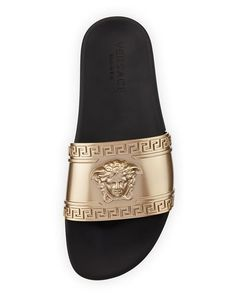 Versace slide sandal with embossed signature Medusa head and Greek key motifs. Metallic golden rubber strap. Tonal logo embossed on contrast rubber sole. Slide-on style. Made in Italy.