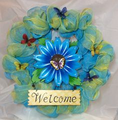 "Blue daisy butterfly wreath.  Metal flower 10x14"" welcome sign and blue, yellow mesh to make 21"" wreath. Butterfly accents . Chenille hanger by KhQualityCreations on Etsy"