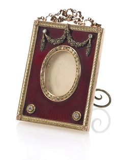 A two-coloured gold, enamel and diamond photograph frame by Fabergé, mark of Mikhail Perkhin, before 1903, St. Petersburg, enamelled in translucent strawberry red enamel over a sunburst guilloché ground and applied on top with double floral swag suspended from two small diamonds, on bottom further applied with laurel leaf rosettes centred with two larger diamonds, crowned with ribbon-tied surmount.