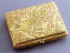Faberge Exhibition - Mythical birds and  scrolling acanthus foliage decorate this two-color gold cigarette-case in the Renaissance taste, the pink matte gold body chased with yellow gold cartouche with a cabochon sapphire pushpiece.  Signed with Imperial Warrant mark, initials of workmaster Oskar Pihl c1850s.