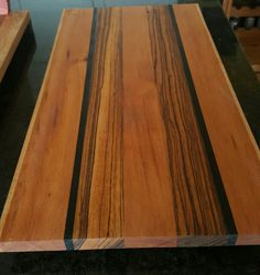 Zebra wood ebony tiger wood. Rimmed with curly maple large board with cedar feet