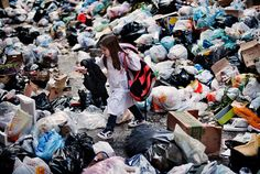 A child walks through uncollected garbage on his way back from school in the historic Spanish district of Naples on November 2010 (Roberto Salomone/AFP Photo)