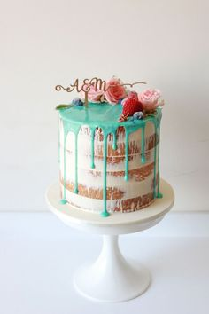 turquoise drip cake topped with flowers
