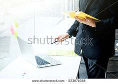 Business man working at office with laptop and documents on his desk, consultant, analyse business situation. Chief checking work. Business office situation. Select focus at hand holding yellow file.