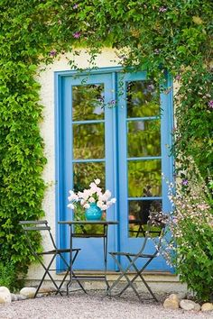 lovely outdoor table, chairs, pea gravel, greenery and french doors