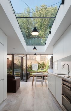 The rear extension to this lower-ground floor flat offers a vista of trees and sky through a long rooflight as well as an adjacent oval version, while full width bi-fold doors create a seamless connection t the beautifully landscaped courtyard garden Modern Kitchen Design, Interior Design Kitchen, Kitchen Designs, Kitchen Contemporary, Interior Garden, Modern House Interior Design, Modern Window Design, Kitchen Ceiling Design, New Ceiling Design
