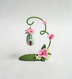 This miniature whimsical pink flower vine with hanging fairy house is a one of a kind original design and creation by artist C. Rohal. It is completely hand made from mixed media, hand sculpted from polymer clay and hand painted and it is wonderful. It measures approximately 1 1/4  in height and it is adorable. It is filled with tiny details. It has been sealed with polycrylic sealer and comes signed/initialed and dated by the artist. It is truly a tiny treasure :)