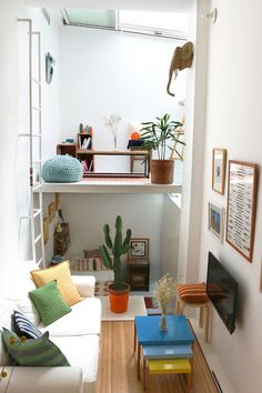 Tiny apartment with wood floor, white walls, gallery wall, white couch, and ladder.