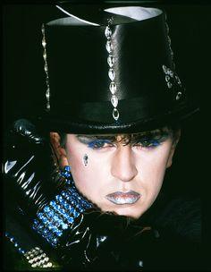 Steve Strange. Blue mascara and silver lipstick. Bejeweled top hat.