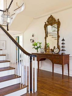 A single piece of furniture and ornate mirror complement the quiet elegance of this formal entryway, leaving the eye to take in the delicate architectural features of the space.