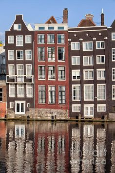 Houses on a canal with reflection on water in Amsterdam, Holland, Netherlands.