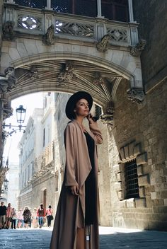 Just The Design: Mafalda Castro in a nude draped maxi coat, simple black dress and a sun hat to accessorise the outfit