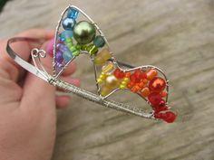 Čelenka do vlasů - motýlková Duha Kostru čelenky tvoří kovová vlnka, na kterou je připevněno drátovaný motýl vypletený skleněnými korálky v barvě duhy. Čelenka je pružná, netlačí. Mohu vyrobit v různých barevných kombinacích - možná barva kostry čelenky stříbrná a černá.  Rozměry motýl: 6,5 x 3 cm