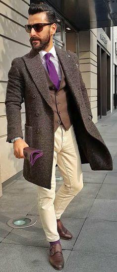 Shop this look on Lookastic: https://lookastic.com/men/looks/overcoat-waistcoat-dress-shirt-chinos-double-monks-tie-sunglasses-watch-socks/12629 — Dark Brown Sunglasses — Purple Gingham Dress Shirt — Purple Tie — Dark Brown Waistcoat — Dark Brown Overcoat — Silver Watch — Beige Chinos — Purple Socks — Dark Brown Leather Double Monks