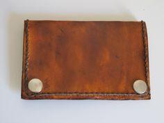 Porta cartão feito em couro, com costura manual e duas divisões.
