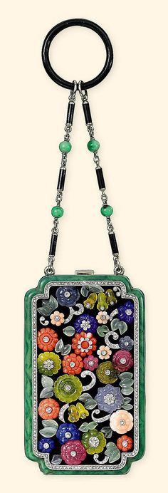 AN ART DECO DIAMOND, MULTI-GEM AND ENAMEL VANITY CASE, BY NOURY MAUBOUSSIN<br />The rectangular-shaped black enamel and gold case with enamelled 'jadeite' border, to the lid mounted with carved multi-gem floral clusters and leaves, each cluster inset with circular-cut diamond collets to the similarly-set scrolling diamond detail, within a millegrain diamond-set border, opening to reveal a fitted mirror, a covered lipstick compartment and a further covered compartment, to the jadeite bead and…