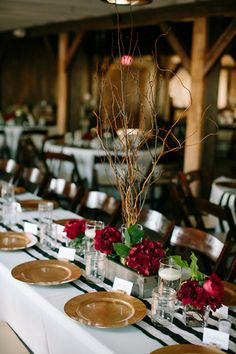 Black and white striped table runners with gold dishware are so pretty, but it's the rose centerpieces in a shade of deep red that sets the scene for this vineyard wedding. | The Windmill Winery in Arizona
