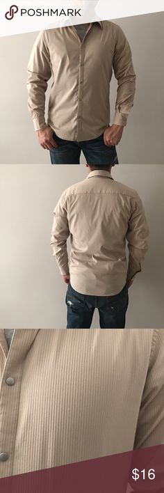 """Armani Exchange Tan Striped Button Front Shirt Armani Exchange. Tan with thin red stripes textured long sleeve snap button front shirt. Sleeve length: 26"""". Materials: 55% cotton, 40% nylon, 5% spandex. Size small with stretch.  Bundle two items to save 10% or create your own bundle and send in an offer! A/X Armani Exchange Shirts Casual Button Down Shirts"""