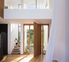 Welcoming you to this modern house is a wooden pivoting front door that opens to a double-height foyer.