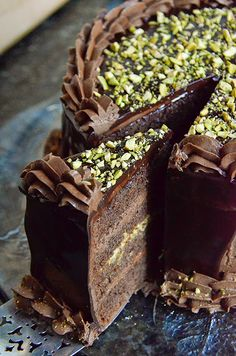 chocolate and pistachio layer cake; moist cocoa sour cream butter cake filled with a sweet homemade pistachio paste whipped cream; covered in a cocoa american buttercream and a semi sweet ganache