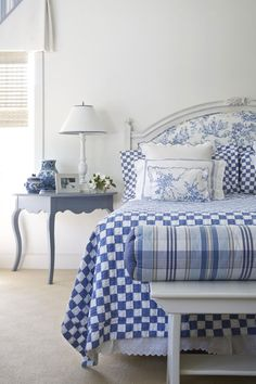 This is just lovely. The blue and white pottery adds interest. Like the bench at the end of the bed and the headboard has fabric that ties to one of the pillows.