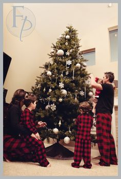 family hanging ornaments on Christmas tree