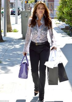 Lisa Vanderpump's 'out for shopping' look. A sheer lace blouse showing her black bra paired with black trousers and stilettos.