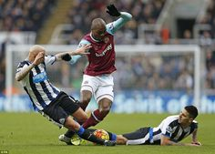 Ogbonna is brought to the floor by the Newcastle tag team of Shelvey (left) and Mitrovic (right) as the hosts looks to secure three points