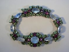 Dorrie Nossiter gem set bracelet and ear clips. an Arts and Crafts moonstone, peridot and rhodolite garnet bracelet and ear clips suite, English, circa 1930, unmarked, the silver and gold bead decorated bracelet 18 cm long, with box clasp, the matching ear clips 2 cm long, ear clips stamped 'Silver'. Sold by John Kelly 1880+. Image 2 of 6.