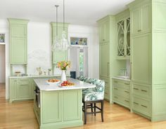 Charming green kitchen features two Hudson Valley Lighting Washington Pendants hung over a honeydew green island fitted with a microwave drawer mounted beneath a white marble countertop seating green print upholstered counter stools.