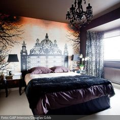 Eine Mischung aus Graf Dracula und Märchenschloss: Das Schlafzimmer mit der aufwändigen Wandgestaltung durch das aufgemalte Betthaupt mischt barocke Elemente mit dunklen Farben.