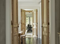 natural wood, and pronounced moldings on these elegant french doors contrast beautifully with the white interior.