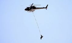 A helicopter transports a motorcycle of a competitor after an accident