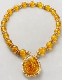 SOLD. Medium size amber beads with gold filled wire creating a framed amber pendant.