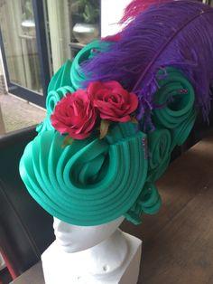 Groene hoge pruik met roze parels, bloemen en veren. Green high wig with pink pearls, flowers and feathers.